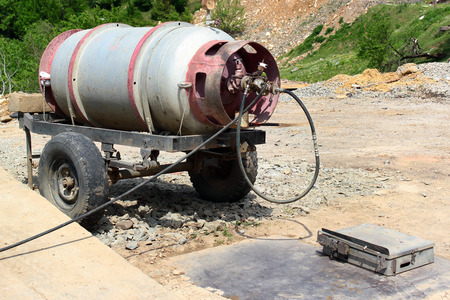 Old propane tank on trailer at a gas station, with scales for weighing the barrels during refilling. Kutaisi, Georgia.