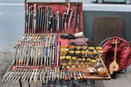 TBILISI, GEORGIA - APRIL 29, 2017: Traditional Georgian souvenirs - daggers, cups, knives and panduri on display at street market near Dry Bridge in Tbilisi. Editorial