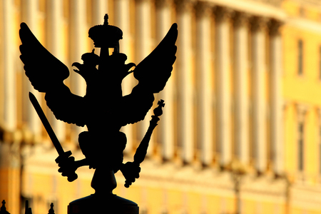 double headed: SAINT PETERSBURG, RUSSIA - JULY 4, 2017: Silhouette of bronze double-headed eagle, symbol and coat of arms of Russia. Fragment of fence around the Alexander Column on Palace Square.