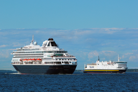 TALLINN, ESTONIA - JULY 7, 2017: MS Prinsendam, a cruise ship for Holland America Line meets the cargo ferry Sea Wind of Estonian company Tallink.