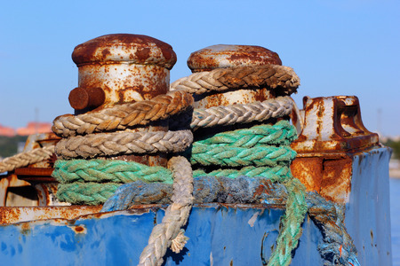 Old rusty bollard with rope on a vessel