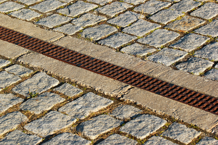 Rainwater drainage grid in a cobbled pavement Stock Photo