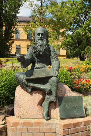 RIGA, LATVIA - JULY 10, 2017: Statue of the painter Irbite (Voldemars Irbe)sitting with sketchbook on a rock. A popular Latvian artist often went barefoot and wore frock coat in all seasons.