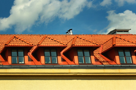 Small dormer windows in a red tiled roof against blue sky background