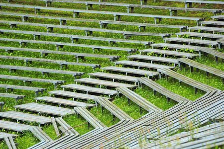 Abandoned wooden benches and bleachers in grass at old rural stadium Stock Photo