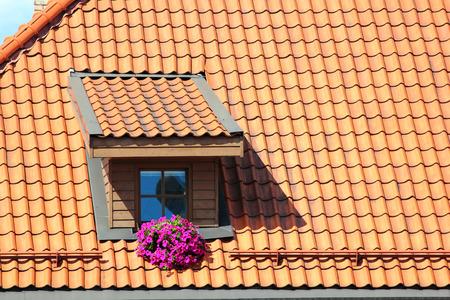 Attic window in orange tiled roof Stock Photo