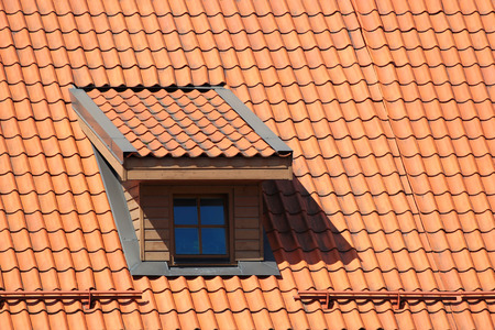 Attic window in orange tiled roof Stock Photo