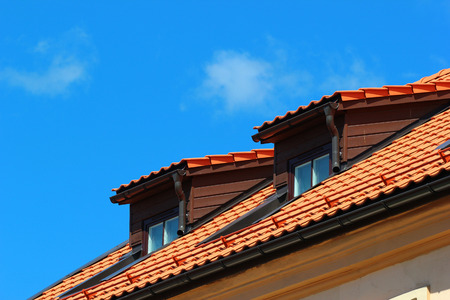 Attic windows in orange tiled roof on blue sky background