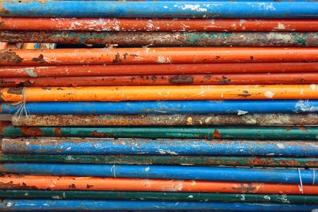 dismantle: Dirty rusty steel pipes with flaking paint as industrial background