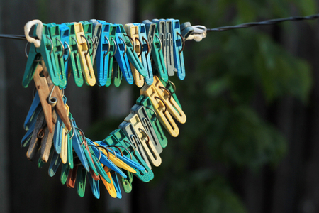 Old clothes pegs hanging on a rope Stock Photo