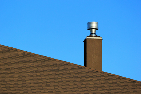 Metal chimney on the roof against blue sky