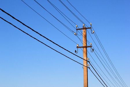 Wires and power line insulators on an electrical pole Stock Photo