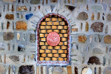 Decorative bricked window in a stone wall