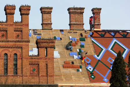 Chernivtsi, Ukraine - December 21, 2017: Workers replace roof tiles on National University building, former residence of Bukovina Metropolitans, included in UNESCO World Heritage List.