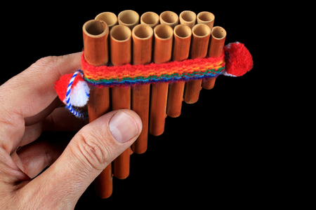 Hand holding a pan flute, isolated on black background