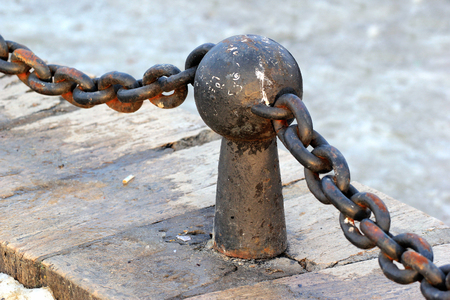 Rusty post of decorative metal fence with chain Stock Photo