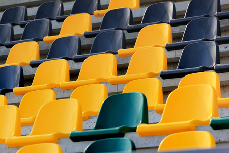 Rows of plastic black and yellow seats at a stadium