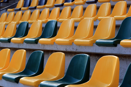 Rows of plastic yellow and green seats at a stadium Banco de Imagens