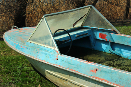 Old abandoned motor boat filled with dirty water