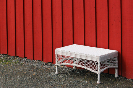 Empty white plastic woven table at red wooden wall Reklamní fotografie