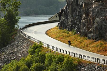 Biker rides on coastal road along Erfjorden, Rogaland county, Norway Reklamní fotografie