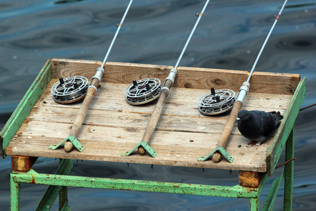 Old fishing tackle, rods with lines and reels. Angling equipment left on a self-made platform.