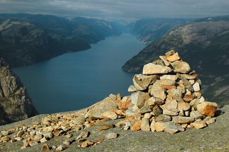 Stone cairn on Neverdalsfjell mountain over Lysefjord and Preikestolen rock, Norway Standard-Bild
