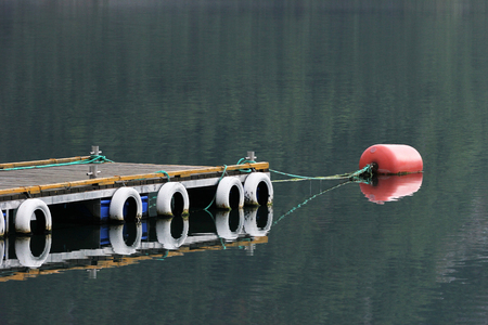 Old pier with white rubber tires and floating red plastic barrel