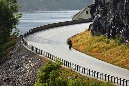 Biker rides on coastal road along Erfjorden, Rogaland county, Norway 写真素材
