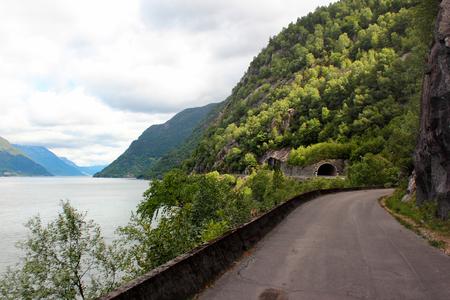Coastal road along the rocky shores of Hardanger fjord, Hordaland county, Norway 写真素材