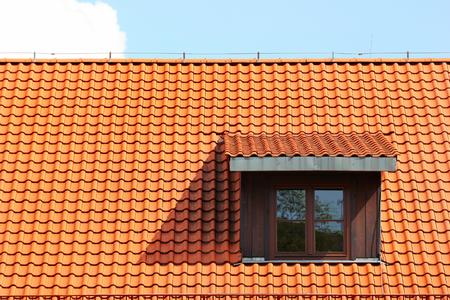 Attic window in orange tiled roof Archivio Fotografico