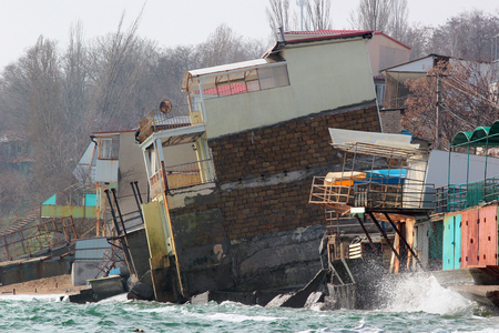 Coastal erosion - houses built on weak clay soil slide down to the sea and collapse near Odessa, Ukraine