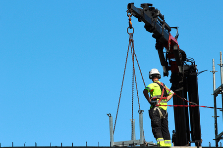 Rigger is helping the crane, keeping right balance and direction. Reklamní fotografie - 120029887
