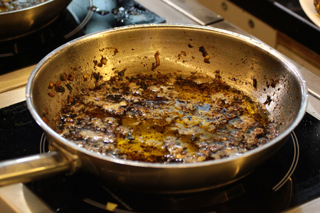 Frying pan with used oil on a stove after cooking