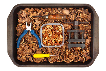 Walnut kernels and shells with tools in a tray, isolated on white background