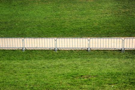 A footpath on green grass behind movable metal fence Reklamní fotografie