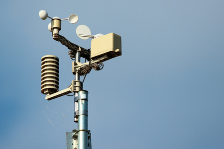 Weather station instruments against blue sky background