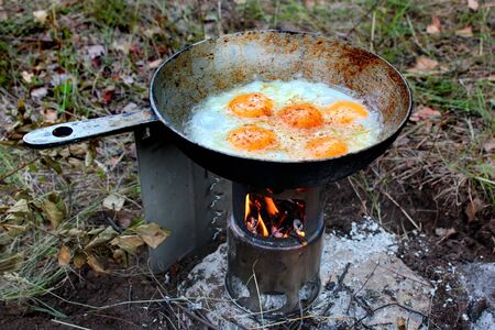 Fried eggs on small portable wood stove Stockfoto