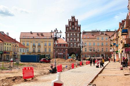 Bartoszyce, Poland - May 6, 2019: View of main Constitution square with Lidzbark Gate in the center of Bartoszyce,  Warmian-Masurian Voivodeship, Poland