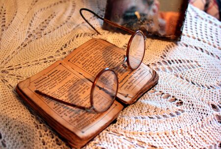 Romankowo, Poland - May 6, 2019: Old Polish Bible, retro spectacles and vintage mirror on a tablecloth. Old age, senility and poverty concept.
