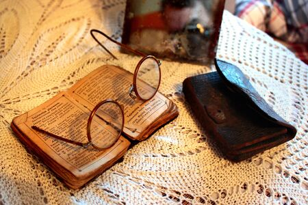 Romankowo, Poland - May 6, 2019: Old Polish Bible, retro spectacles, purse and vintage mirror on a tablecloth. Old age, senility and poverty concept. Editöryel