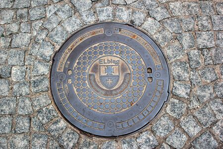 Elblag, Poland - May 9, 2019: A manhole cover of Elblag waterworks in the renovated historical Old Town. Editöryel