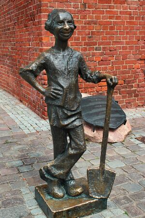 Elblag, Poland - May 9, 2019: A monument of Piekarczyk (Little Baker) next to the Market Gate. According to legend, he saved the town from Teutonic order knights.