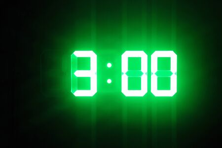 Green glowing digital clocks in the dark show 3:00 time