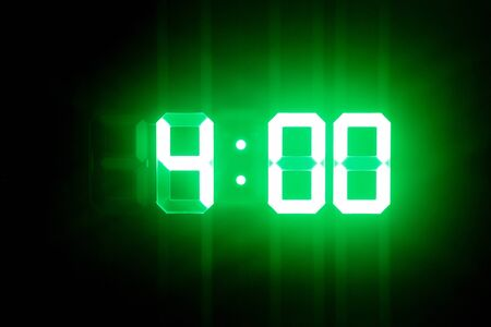 Green glowing digital clocks in the dark show 4:00 time