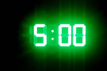 Green glowing digital clocks in the dark show 5:00 time Stock Photo