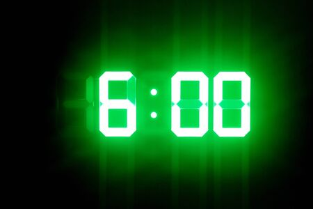 Green glowing digital clocks in the dark show 6:00 time