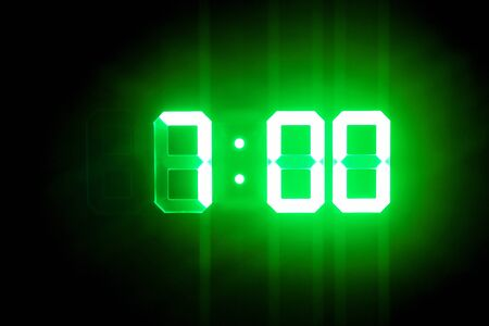 Green glowing digital clocks in the dark show 7:00 time