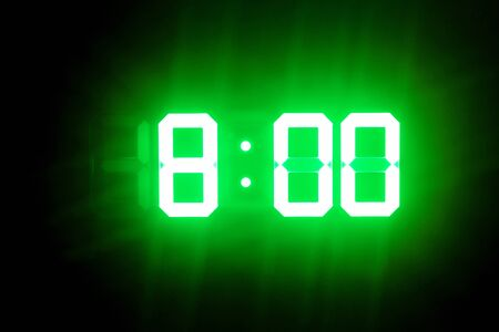 Green glowing digital clocks in the dark show 8:00 time
