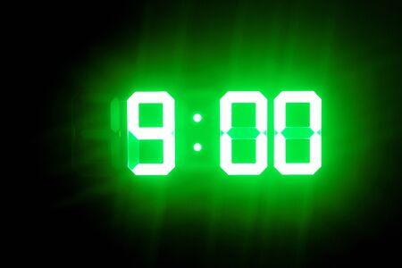 Green glowing digital clocks in the dark show 9:00 time Stock Photo